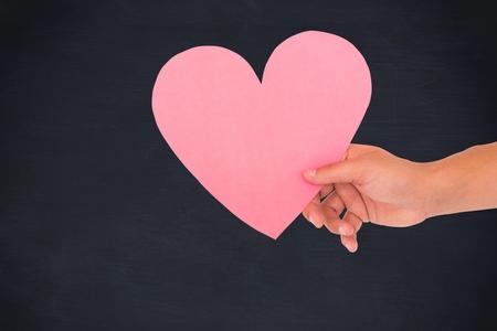 hand holding paper: hand holding paper hart with black background Stock Photo