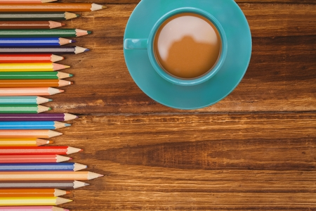 Cup of coffee with pencils on desk with copy space