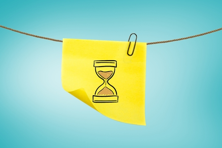 elapsed: digital composite of hourglass on post-it with blue background Stock Photo