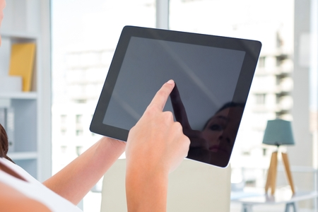 Composite image of woman's hands holding tablet computer with house background