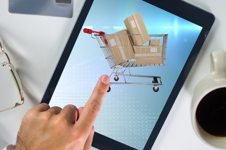 Composite image of hand touching a screen of tablet computer for e commerce