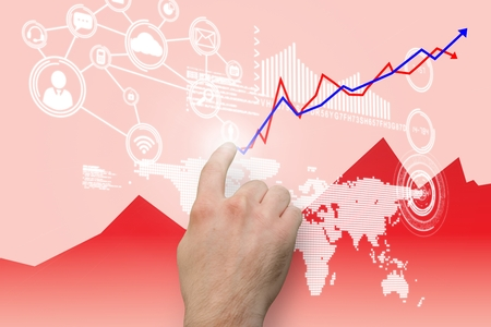 hand pointing: composite of hand pointing at upward graph over red background Stock Photo