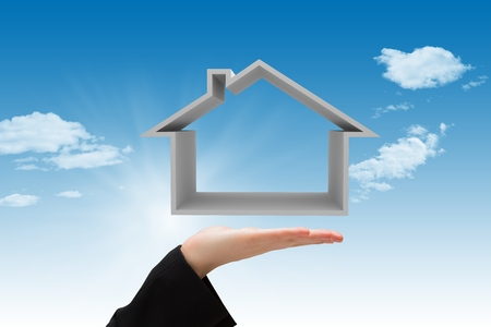 Composite image of hand carrying house with sky background