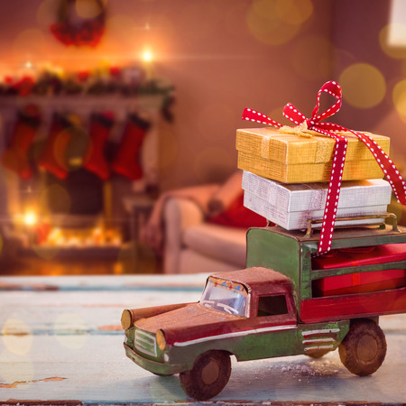 Car toy on wooden surface against fireplace decorate with christmas decor and ornaments Stock Photo