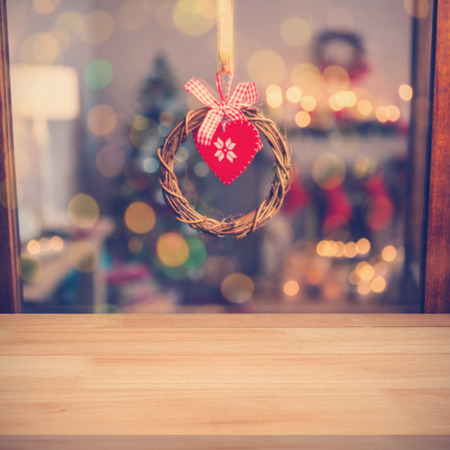 A brown parquet against christmas grapevine wreath with ribbon hanging on window