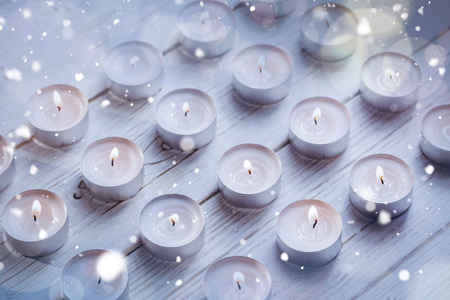 burning time: Candles burning on wooden table during christmas time