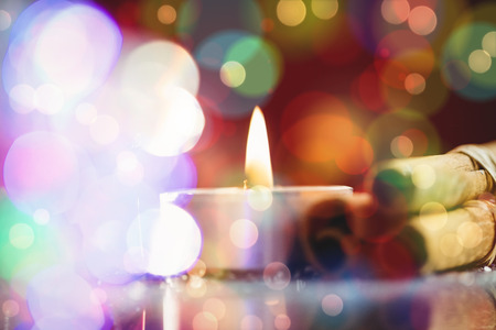 lit candle: Cinnamon stick and lit candle during christmas time Stock Photo