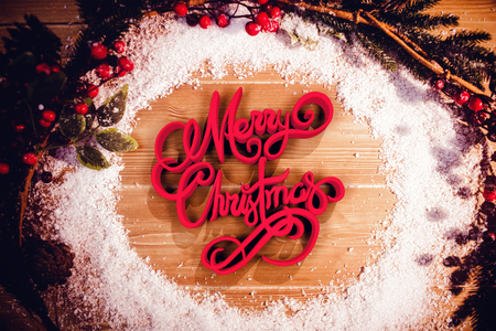 Dreidimensional des Textes der frohen Weihnachten in der roten und weißen Farbe gegen Dekorationen auf Holztisch