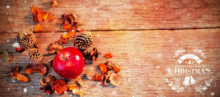 wooden plank: Christmas greeting  against apple and pine cone on wooden plank Stock Photo