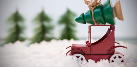 fake christmas tree: Toy car carrying christmas tree on fake snow during christmas time