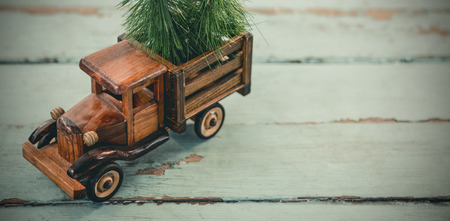 Toy tempo carrying christmas fir on wooden plank during christmas time
