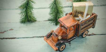 Toy tempo carrying christmas present on wooden plank during christmas time Reklamní fotografie