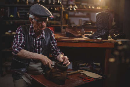 outsole: Shoemaker repairing a shoe in workshop