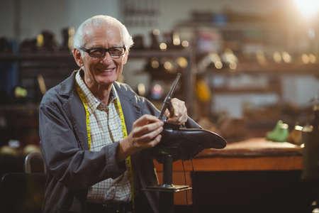 hammering: Portrait of smiling shoemaker hammering on a shoe in workshop