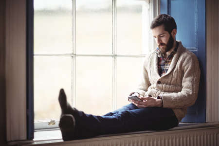 window sill: Man using mobile phone while sitting on window sill at home