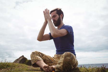 performing: Man performing yoga on cliff