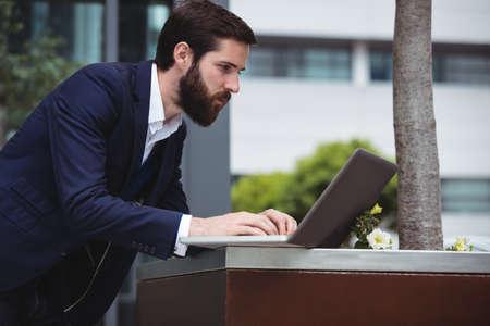 attentive: Attentive businessman using laptop outside office