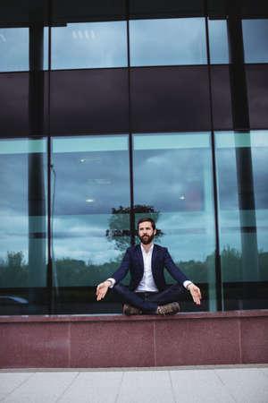 yoga outside: Businessman practicing yoga outside office building LANG_EVOIMAGES