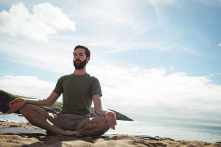 performing: Man performing yoga on beach