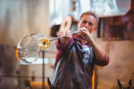 Glassblower shaping a glass on the blowpipe at glassblowing factory LANG_EVOIMAGES