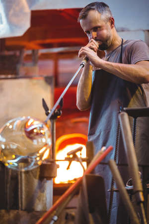 creating: Glassblower shaping a glass on the blowpipe at glassblowing factory LANG_EVOIMAGES