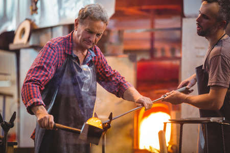Glassblower forming and shaping a molten glass at glassblowing factory LANG_EVOIMAGES