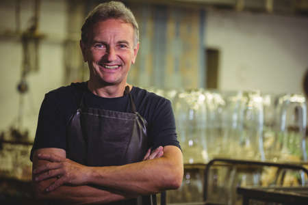 glassblower: Portrait of glassblower with arms crossed at glassblowing factory LANG_EVOIMAGES