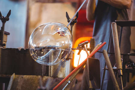 glassblower: Glassblower shaping a glass on the blowpipe at glassblowing factory LANG_EVOIMAGES