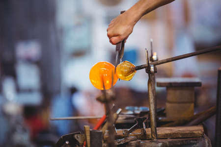 glassblower: Glassblower shaping a molten glass at glassblowing factory