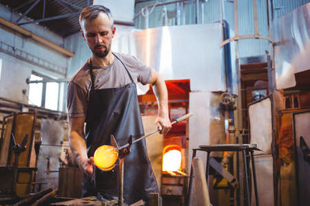 molten: Glassblower forming and shaping a molten glass at glassblowing factory LANG_EVOIMAGES