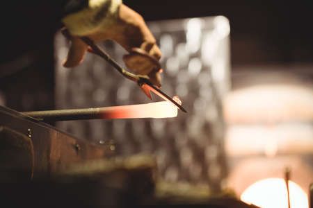 molten: Glassblower working on a molten glass at glassblowing factory
