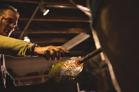 molten: Glassblower shaping a molten glass at glassblowing factory