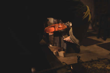 blowpipe: Glassblower forming and shaping a molten glass at glassblowing factory LANG_EVOIMAGES