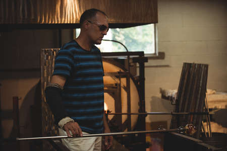 blowpipe: Glassblower shaping a molten glass at glassblowing factory