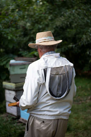 Rear view of beekeeper holding the beehive in wooden frame at apiary garden