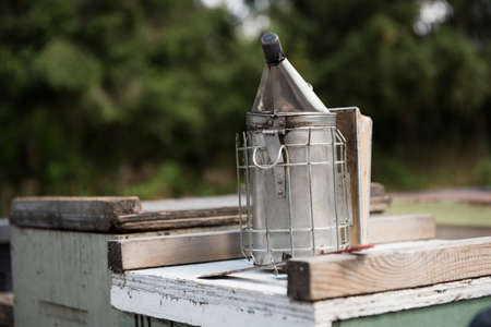 Bee smoker on wooden box in apiary garden LANG_EVOIMAGES