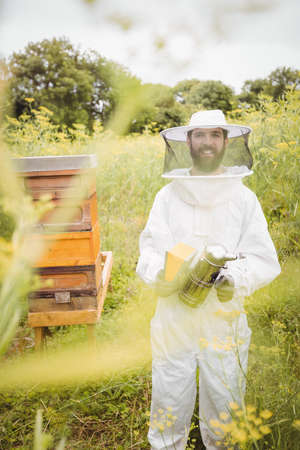 smoker: Portrait of beekeeper holding bee smoker in the field