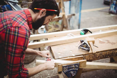 Man using a handheld tool to smooth and level the surface of a plank in boatyard
