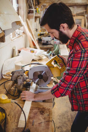 electric saw: Man cutting wooden plank with electric saw in boatyard LANG_EVOIMAGES