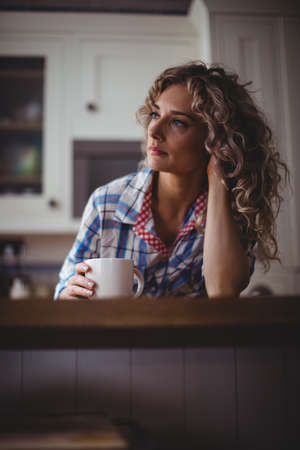 mid thirties: Thoughtful woman having coffee in kitchen at home
