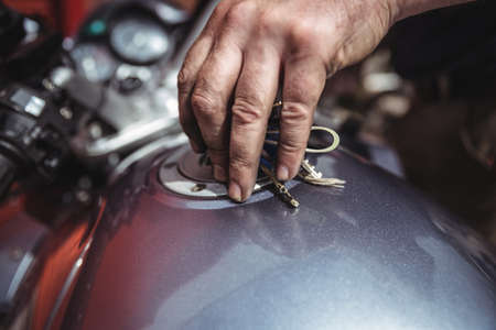 fuel tank: Hand of mechanic closing a fuel tank of motor bike at workshop LANG_EVOIMAGES