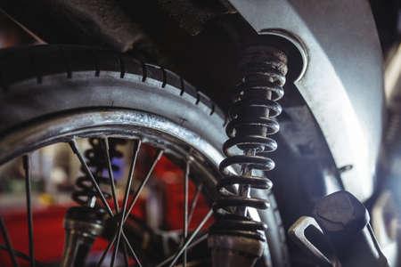 damper: Close-up of motorbike shock absorber in workshop LANG_EVOIMAGES