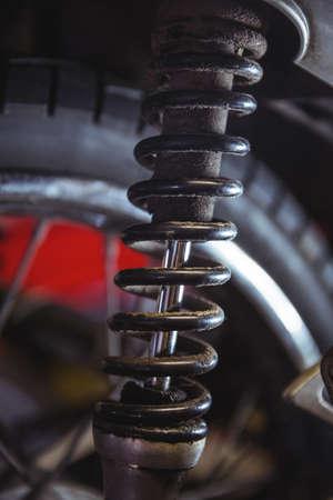 shock absorber: Close-up of motorbike shock absorber in workshop LANG_EVOIMAGES