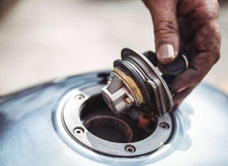 tanque de combustible: Mano del mecánico de abrir un depósito de combustible de la moto en el taller LANG_EVOIMAGES