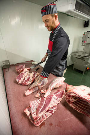 karkas: Butcher cutting the ribs of pork carcass in butchers shop