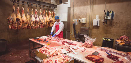 storage room: Butcher chopping meat in storage room at butchers shop