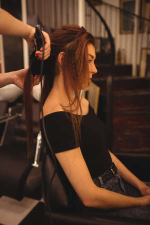 hair saloon: Woman is getting her hair straightened at hair saloon