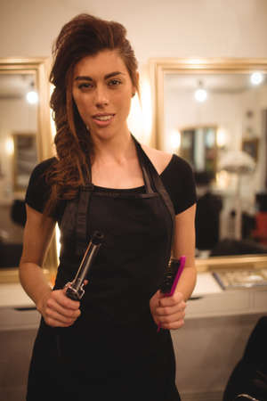 curler: Female hairdresser holding hair curler machine and hairbrush at saloon LANG_EVOIMAGES