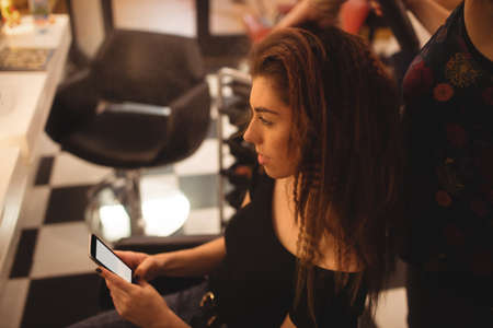 hair saloon: Woman using mobile phone while getting her hair straightened at hair saloon