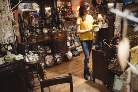 antique shop: Woman looking at a vintage teapot in antique shop